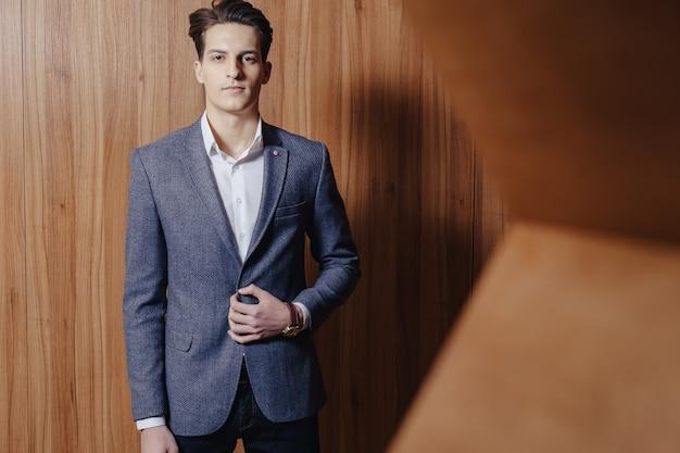 Стильный парень в куртке в офисе на простом деревянном фоне