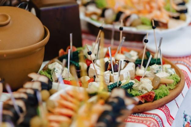 結婚式やその他のイベントを祝うためのお祝いの塩味のビュッフェ、魚、肉、チップ、チーズボールやその他の料理