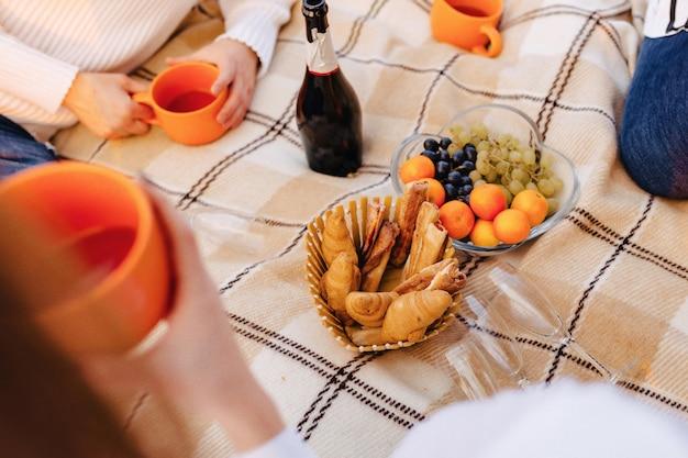 フルーツ、ワイン、紅茶、カップ、クロワッサン、お菓子などの敷物の上の夏のピクニック