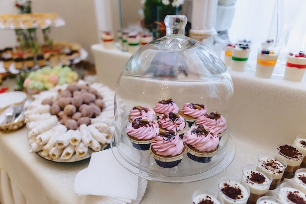 Сладкий праздничный фуршет, фрукты, шапки, макароны и сладости