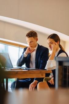 若いビジネスマンの男の子と女の子はラップトップで動作します