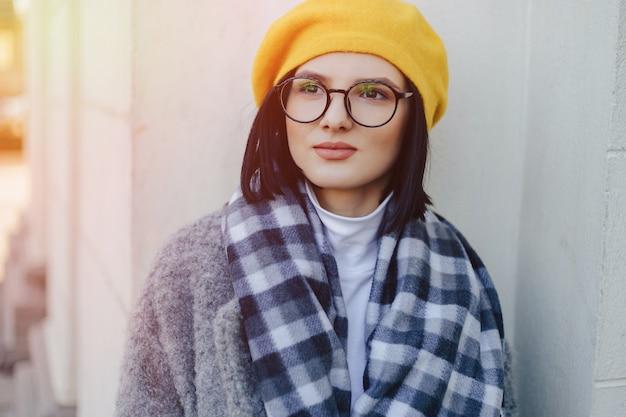 コートとシンプルな明るい背景に黄色のベレー帽のメガネで魅力的な若い女の子