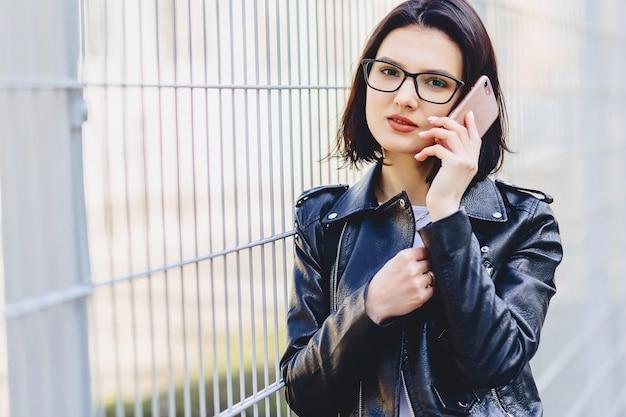 電話で話しているメガネの革のジャケットの女