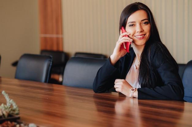 オフィスや観客の電話で机に座ってビジネススタイルの服の若い魅力的な感情的な女の子