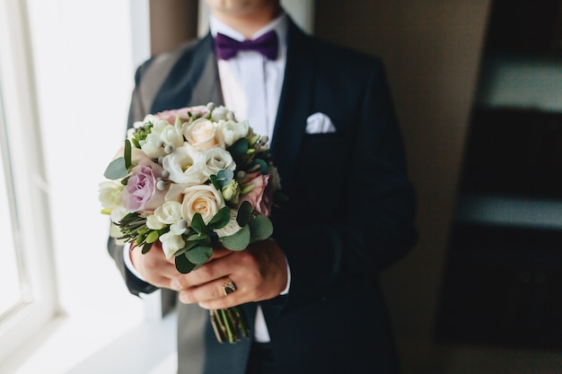 Жених держит в руках свадебный букет