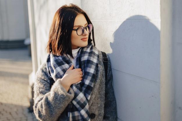 Привлекательная молодая девушка в очках в пальто, ходить в солнечный день