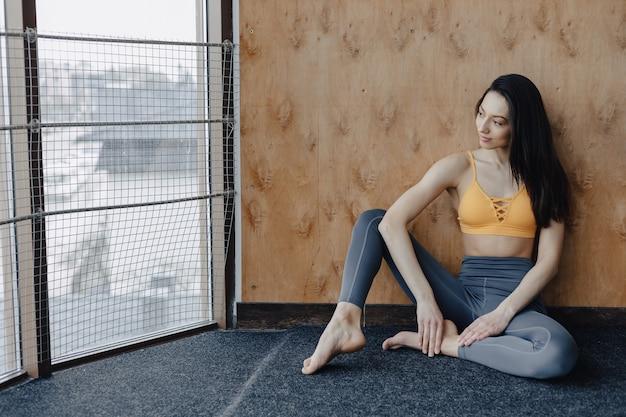木製の壁の背景の窓の近くの床に座って、ヨガのクラスで休む若い魅力的なフィットネス女の子