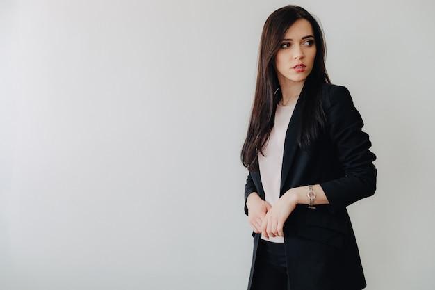 オフィスや観客の真っ白な背景にビジネススタイルの服の魅力的な感情的な少女