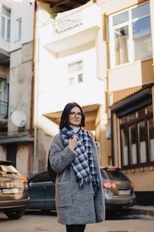 Привлекательная позитивная молодая девушка в очках в пальто на улице
