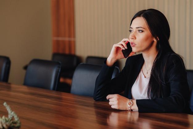 オフィスや観客の携帯電話で机に座ってビジネススタイルの服の若い魅力的な感情的な女の子
