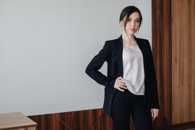 Молодая привлекательная эмоциональная девушка в деловом стиле одежды в офисе или аудитории