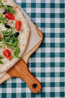 マグロ、チーズ、ルッコラ、バジル、トマト、オリーブ、ナポリのピザ、テキストのための場所でセルのテーブルクロスの木製テーブルにチーズを振りかけた。