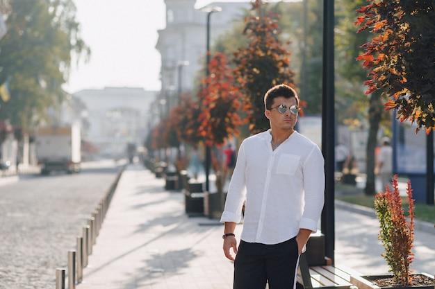 晴れた日にヨーロッパの街を歩いてシャツのスタイリッシュな若者