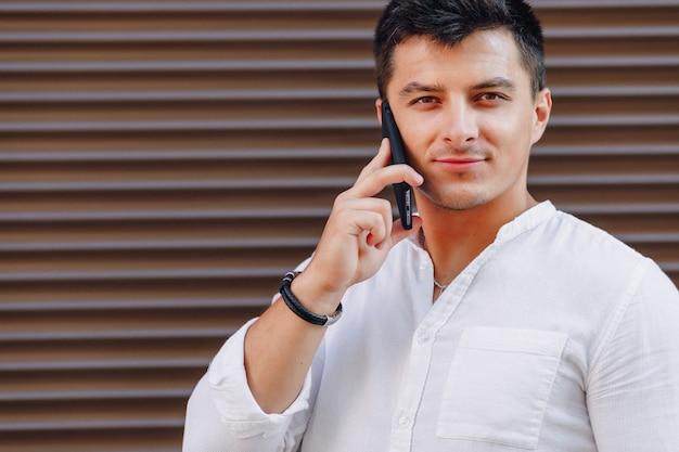 シンプルな表面に電話で話しているシャツの若いスタイリッシュな男