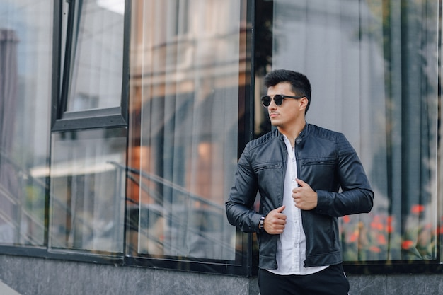 Молодой стильный парень в очках в черной кожаной куртке на стеклянной поверхности