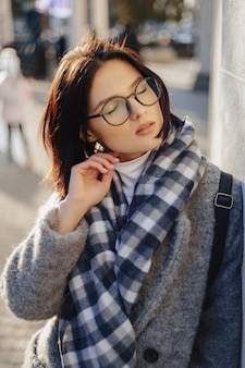 晴れた日に歩いてコートで眼鏡をかけている魅力的な若い女の子