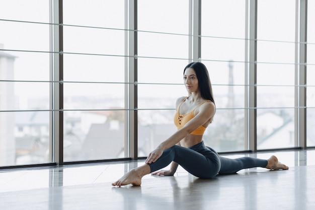 パノラマの窓の表面に対して床にヨガでフィットネス演習を行う若い魅力的な女の子