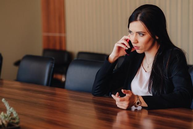 Молодая привлекательная эмоциональная девушка в деловой стиль одежды, сидя за столом с телефоном в офисе или аудитории