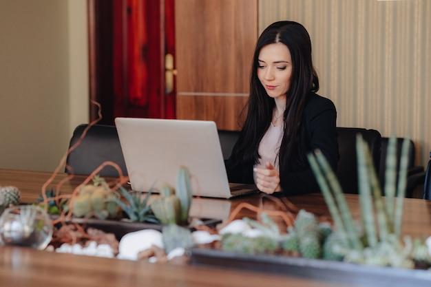 Молодая привлекательная эмоциональная девушка в деловом стиле одежды, сидя за столом на ноутбуке и телефон в офисе или аудитории