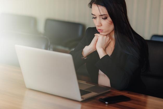 ノートパソコンとオフィスや講堂で携帯電話の机に座ってビジネススタイルの服の魅力的な感情的な少女