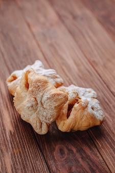 新鮮な甘いペストリーに砂糖の粉を木製の表面に振りかけます