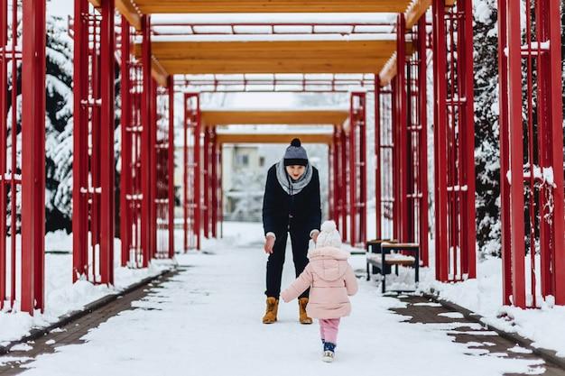 幸せな若い家族は、ウィンターストリート、ママ、パパ、子供に赤ちゃんと一緒に歩きます