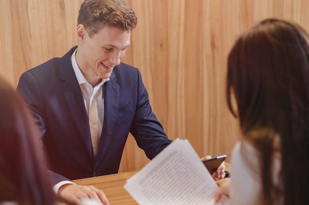 ジャケットとシャツを着た男は同僚と机に座って、オフィスでドキュメントを操作します