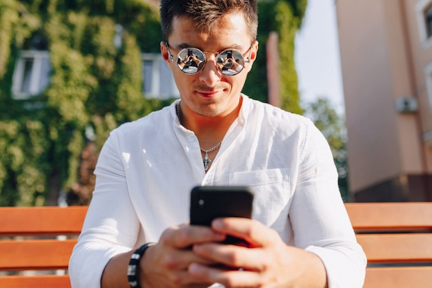 Молодой стильный парень в рубашке с телефоном на скамейке в солнечный теплый день на открытом воздухе