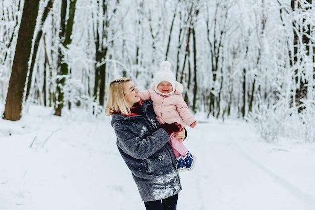 冬の通りで歩く赤ちゃんとスタイリッシュなお母さん