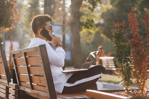 携帯電話と晴れた暖かい日の屋外、フリーランスのベンチでノートブックとシャツのスタイリッシュな若者