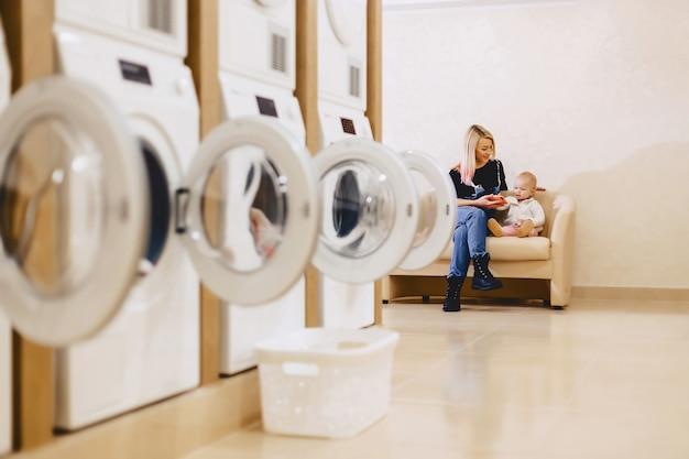 子供を持つ女性が待っている洗濯物のソファーに座っています。