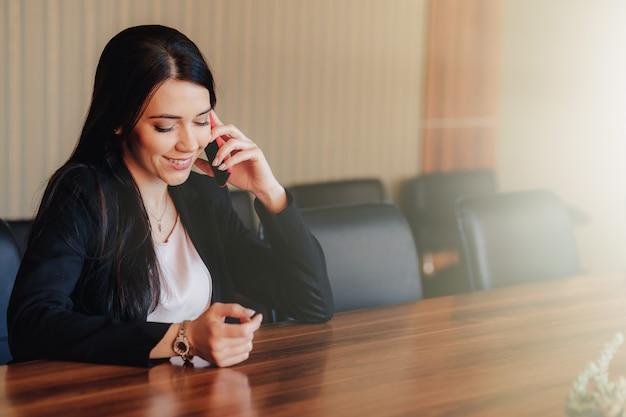 Молодая привлекательная эмоциональная женщина в одежде стиля дела сидя на столе с телефоном