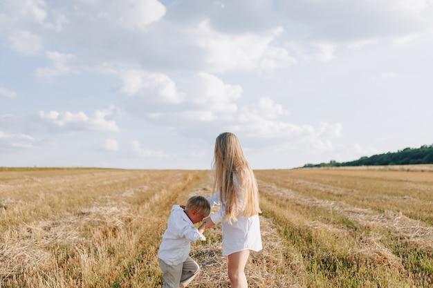 Белокурый мальчик играя с мамой с белыми волосами с сеном в поле. лето, солнечная погода, сельское хозяйство. счастливое детство