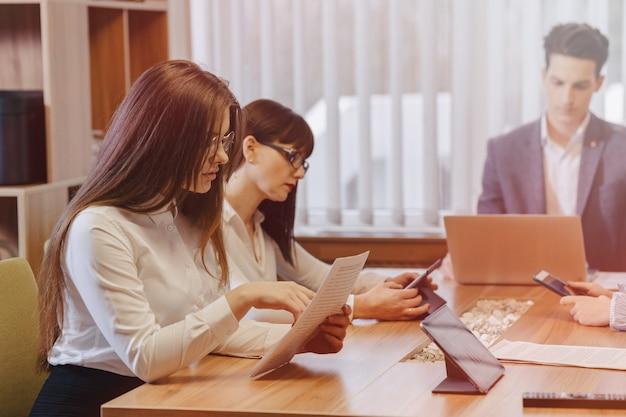 Стильные молодые люди в современном офисе работают за одним столом с документами и ноутбуком