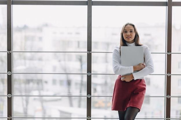 Хорошенькая молодая девушка с ноутбуком у окна в офисе с большими окнами. концепция удаленной работы. фрилансер работает один.