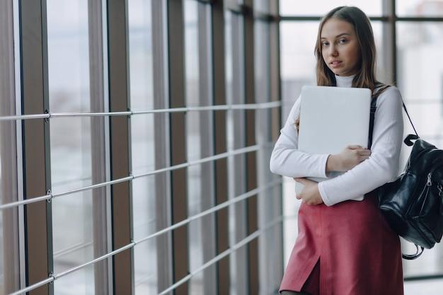 魅力的な女の子は、ノートパソコンと空港ターミナルやオフィスのもので明るい廊下を歩きます。旅行の雰囲気または代替の仕事の雰囲気。