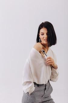 無地の壁でポーズ化粧ブラシで魅力的な若いビジネスの少女。メイクや化粧品のコンセプトです。
