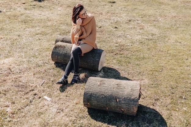 晴れた日に電話で森の壁に自然に魅力的なスタイリッシュな少女。屋外の休日とテクノロジーへの依存。