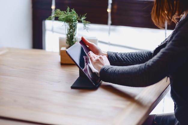 メガネの女の子は、テーブルのクローズアップでタブレットの画面を拭く
