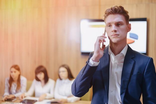 Стильный молодой бизнесмен носить пиджак и рубашку на фоне рабочего офиса с людьми, разговаривающими по мобильному телефону