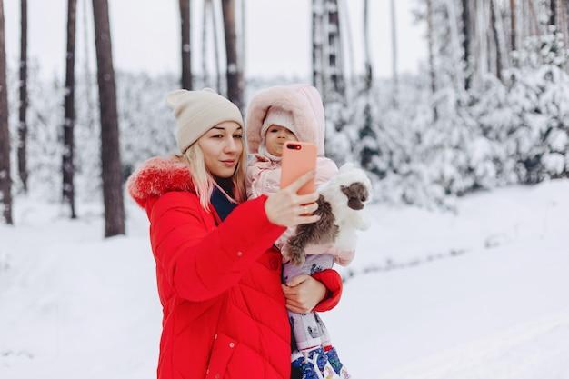 ママは赤ん坊を両腕に抱きしめ、雪に覆われた場所で自分撮りをする