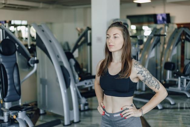 魅力的なスポーツ少女は、ジムのシミュレーターの壁に立っています。健康的な生活様式。
