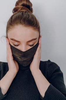 Молодая привлекательная девушка на светлой стене носит медицинскую маску. использование личной защиты. противоэпидемическая и противозадирная защита человека.