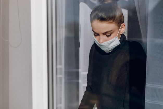 防護マスクの魅力的な少女は窓の外に見えます。流行時の隔離。自宅隔離。