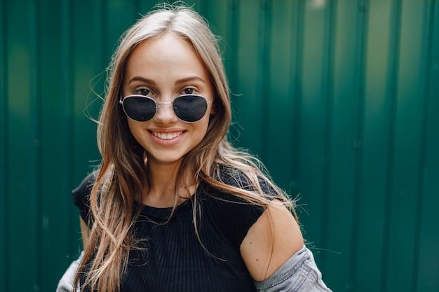 テキストのための場所でシンプルな濃い緑の壁にメガネのデニムの服のかなり魅力的な少女。