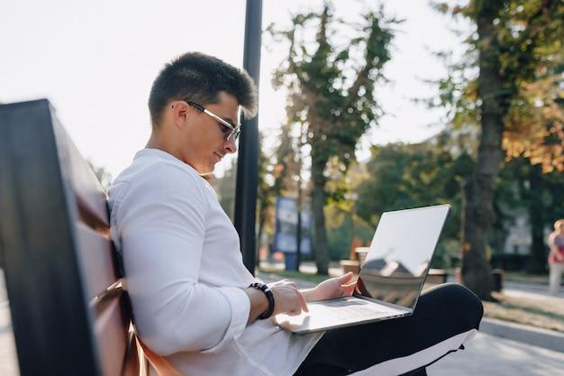 電話と晴れた暖かい日の屋外、フリーランスのベンチでノートブックとシャツのスタイリッシュな若者