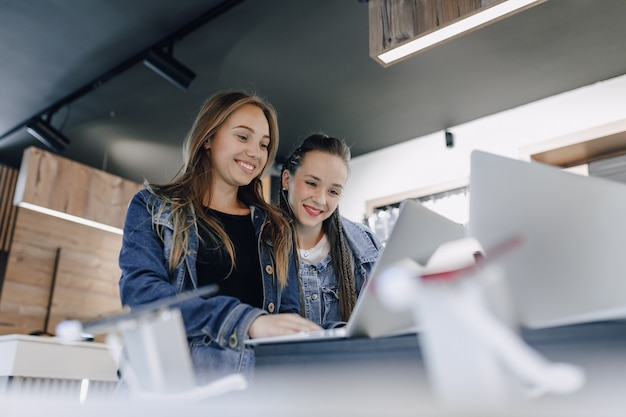 電器店の魅力的な若い女の子は、展示会でラップトップを使用しています。ガジェットの購入の概念。