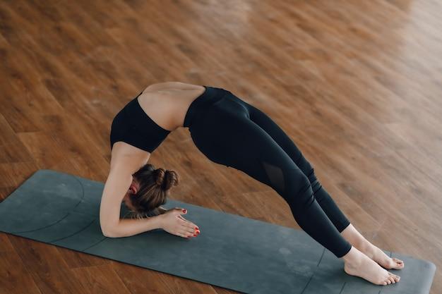 Довольно привлекательная девушка делает йогу в светлой комнате