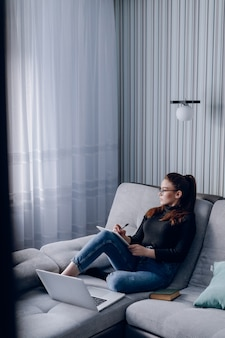 自宅のラップトップでソファで働く魅力的な少女。家にいる間の快適さと居心地の良さ。ホームオフィスと在宅勤務。リモートのオンライン雇用。