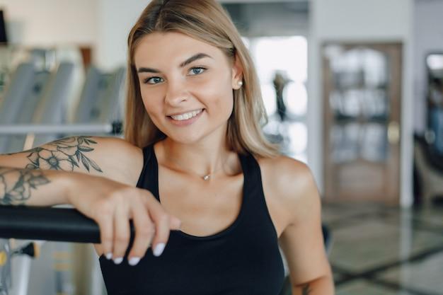 Привлекательная спортивная девушка, стоя возле тренажеров. здоровый образ жизни.
